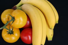 Stilleben. Bananas together with yellow and red tomatoes - black background Stock Photography