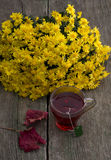 Stilleben bukett av gula blommor, genomskinlig kopp te Arkivbild