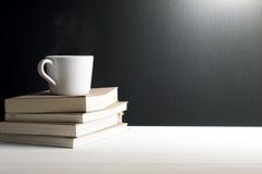 Stilleben - en kopp av varmt kaffe på böcker Arkivbild