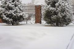 Stilleben en vinterborggård, ett staket av metall och bruten granit, filialer av gran i snön under ett snöfall arkivfoto