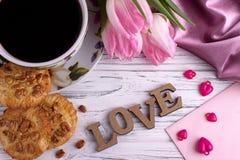 Stilleben för dag för valentin` s elegant med tulpanblommakoppen av tecknet för förälskelse för coffemarshmallowbokstäver på vit  Arkivbilder