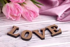 Stilleben för dagen för valentin` s älskar elegant med rosa tyg för tulpanblommor och bokstäver tecknet på vit träbakgrund Arkivbild