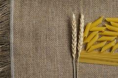 Stilleben för ett kök av veteöron och pasta från vete på en säckvävbakgrund som göras i Kasakhstan royaltyfria bilder
