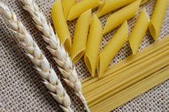 Stilleben för ett kök av veteöron och pasta från vete på en säckvävbakgrund som göras i Kasakhstan royaltyfri foto