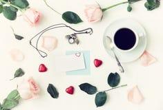 Stilleben för St-valentindag i retro signaler - koppen kaffe, rosor, det tomma kortet, den uggla formade klockan, hjärta formade  Arkivbild