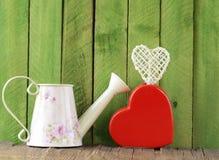 Stilleben för valentin dag - keramisk hjärta och att bevattna kan Arkivfoto