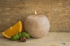 Stilleben från en apelsin, en stearinljus och en kanel Royaltyfri Fotografi