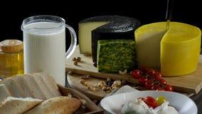 Stilleben i den gamla stilen med en tillbringare och rånar av mjölkar, huvud av ost, rostat bröd, honung och ägg på svart bakgrun royaltyfria bilder