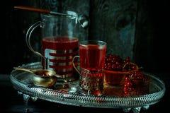 Stilleben i kunglig stil för tappning Exponeringsglas med rött aktuellt te eller frukt-drinken på silverdisk arkivfoton