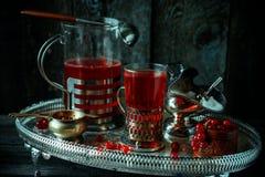 Stilleben i kunglig stil för tappning Exponeringsglas med rött aktuellt te eller frukt-drinken på silverdisk royaltyfri bild