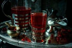 Stilleben i kunglig stil för tappning, med rött aktuellt te eller frukt-drinken på silverdisk royaltyfri fotografi