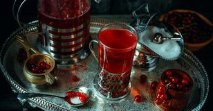 Stilleben i kunglig stil för tappning Stäng sig upp exponeringsglas med rött aktuellt te eller frukt-drinken på silverdisk, bästa royaltyfri bild