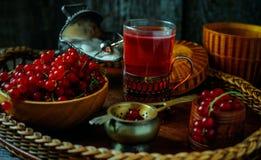 Stilleben i tappningstil Stäng sig upp exponeringsglas med rött aktuellt te eller frukt-drinken och träbunken arkivfoto