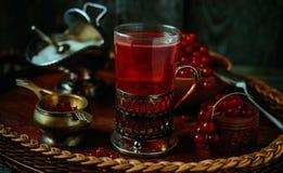 Stilleben i tappningstil Stäng sig upp exponeringsglas och karaffen med rött aktuellt te eller frukt-drinken arkivfoto