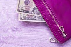 Stilleben i violett stil, lilaläderhandväska och amerikandollar på en träbakgrund Fotografering för Bildbyråer