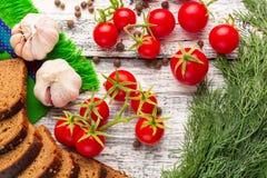 Stilleben: körsbärsröda tomater, svart bröd, vitlök, fänkål, bayber Arkivbilder