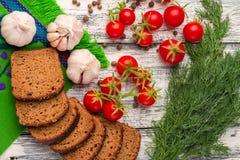 Stilleben: körsbärsröda tomater, svart bröd, vitlök, fänkål, bayber Fotografering för Bildbyråer