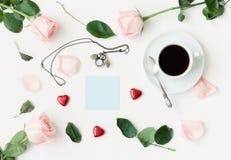 Stilleben - koppen kaffe, persikarosor, blått ark av anmärkningen, den uggla formade klockan, hjärta formade godisar på vit bakgr royaltyfri fotografi