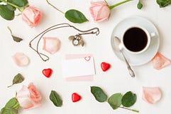 Stilleben - koppen kaffe, persikarosor, det tomma kortet, den uggla formade klockan, hjärta formade godisar på vit bakgrund Royaltyfria Foton