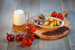 Stilleben med öl, sill, kurerat kött, land-stil potatisar royaltyfri bild