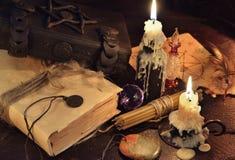 Stilleben med böcker, stearinljus och magi anmärker Arkivbilder