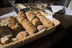 Stilleben med bakelse och bröd i vide- korg på trätabellen med plattor, bunkar och grönsaksallad Royaltyfria Foton