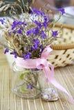 Stilleben med blommor i en genomskinlig bank Arkivbilder