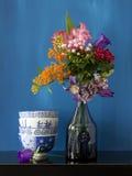 Stilleben med blommor i en vas och någon bowlar nolla Arkivbild