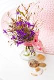 Stilleben med blommor och en hatt Arkivfoton