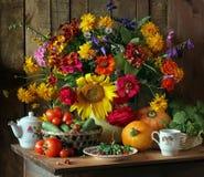 Stilleben med blommor och grönsaker augustly fotografering för bildbyråer