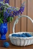 Stilleben med blommor och handarbete i korgen arkivbild
