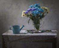 Stilleben med blått som bevattnar kan och en bukett av krysantemum Arkivbilder