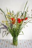 Stilleben med buketten av vildblommor i en vas på en tabell royaltyfri fotografi
