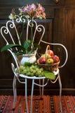 Stilleben med den antika stolen, blommor och frukt Arkivfoto