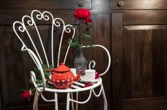Stilleben med den antika stolen, blommor och tea Royaltyfri Bild