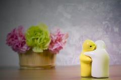 Stilleben med den keramiska dockan och blomman på trätabellen över gru Royaltyfri Fotografi