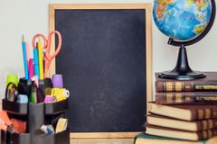 Stilleben med den liljekonvaljgruppen, boken och jordklotet Lärares dagbegrepp royaltyfri bild