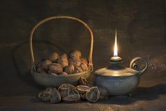 Stilleben med den olje- lampan och valnötter royaltyfri fotografi