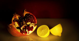 Stilleben med den röda pomegranaten och citronen. Arkivbild