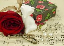 Stilleben med den röda rosen och en staty av en katt Fotografering för Bildbyråer