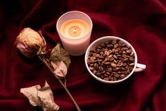 Stilleben med den torkade rosen, stearinljus, kopp kaffebönor Arkivbilder