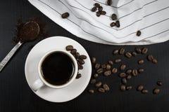 Stilleben med den vita koppen med läckert kaffe och kaffebönor fotografering för bildbyråer