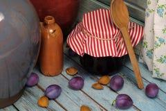 Stilleben med driftstoppkruset, keramiska botles och plommoner Royaltyfri Bild
