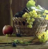 Stilleben med druvor och det röda äpplet Arkivbild