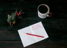 Stilleben med en anteckningsbok med en röd inskrift 2018, en kopp kaffe fotografering för bildbyråer
