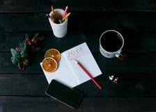 Stilleben med en anteckningsbok med en röd inskrift 2018, en kopp kaffe arkivfoton