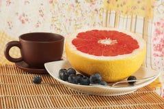 Stilleben med en bantafrukost: grapefrukt, blåbär och något kaffe Fotografering för Bildbyråer