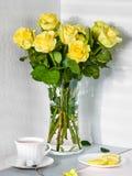 Stilleben med en bukett av gula rosor och en kopp te arkivfoto