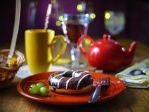 Stilleben med en chokladmunk på en röd handgjord platta, krusbärbär, i bakgrunden per den gula koppen och en röd tekanna för royaltyfri foto
