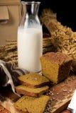 Stilleben med en glass tillbringare av mjölkar, rågbröd, öron av havre Royaltyfria Foton